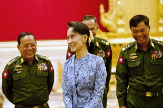 Myanmar's NLD party leader Aung San Suu Kyi smiles with army members during the handover ceremony of outgoing President Thein Sein and new President Htin Kyaw at the presidential palace in Naypyitaw on March 30, 2016. Photo courtesy of REUTERS/Ye Aung Thu/Pool