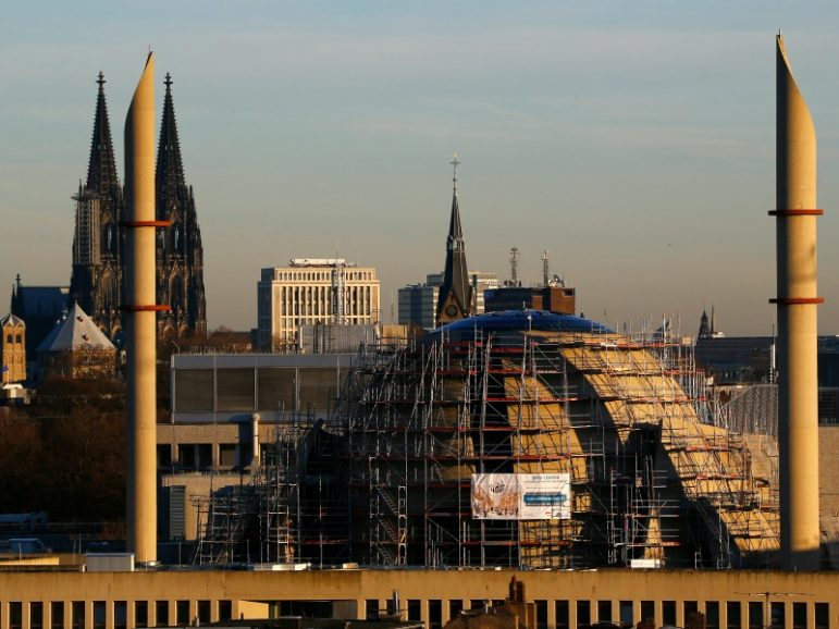 The two 55m high minarettes and the construction site of the new Cologne Central Mosque are seen next to the famous landmark and UNESCO world heritage, the Cologne Cathedral in Germany. Photo courtesy of Wolfgang Rattay/Reuters