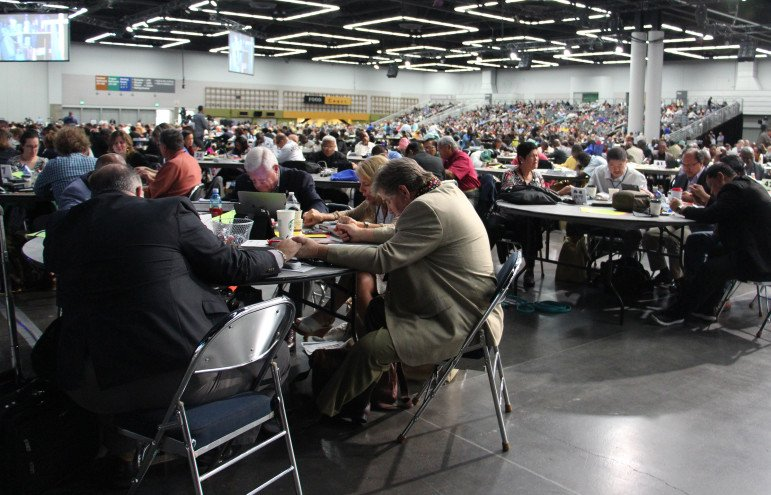 Delegates at the United Methodist Church General Conference in Portland, Ore., spent time in prayer on May 17, 2016 after Bishop Bruce Ough addressed rumors the denomination's Council of Bishops was considering a proposal to split the church. RNS photo by Emily McFarlan Miller