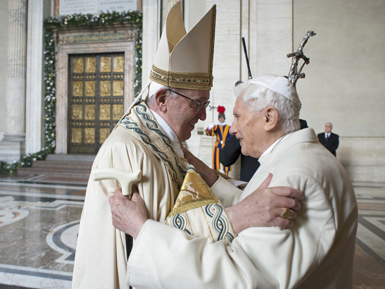 Pope Francis embraces Emeritus Pope Benedict XVI before opening the Holy Door to mark opening of the Catholic Holy Year, or Jubilee, in St. Peter's Basilica, at the Vatican, on Dec. 8, 2015. (Photo by Osservatore Romano/Handout via AP)