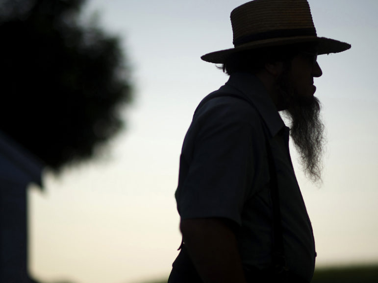 A silhouetted Amish man waits during his buggy tour in Lancaster County, Pa., on Aug. 9, 2014. Photo courtesy of REUTERS/Mark Makela