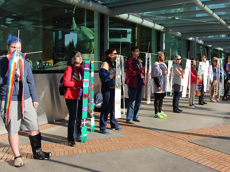 More than 160 demonstrators greeted delegates with a silent protest for LGBT inclusion in the United Methodist Church as they arrived on May 18, 2016, at the Oregon Convention Center for the United Methodist General Conference. Some held crosses draped in stoles from the Shower of Stoles project, each representing the life an LGBT person in ministry. RNS photo by Emily McFarlan Miller
