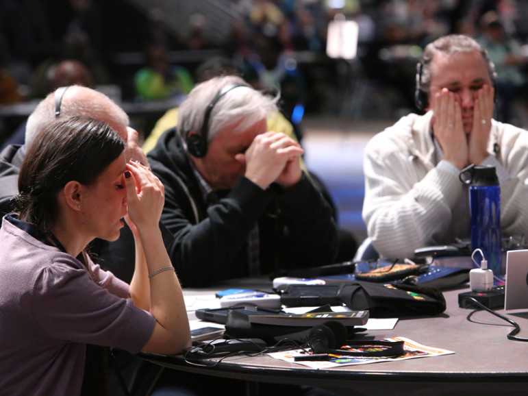 Delegates pause for a moment of prayer at the 2016 United Methodist General Conference. From left, Vasylyna Babych from the Ukraine-Moldava Provisional, and Alexander Pererva and Alexandr Meinikov from the Southern Russia Provisional. Photo by Kathleen Barry, UMNS