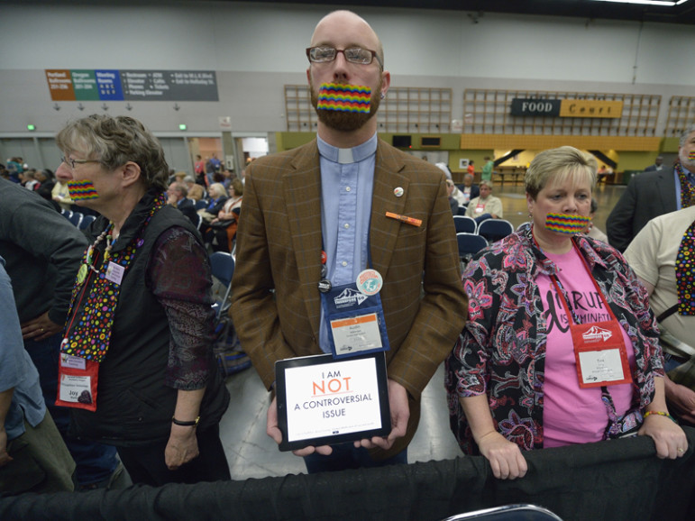 Demonstrators wear rainbow gags on May 14, 2016, to protest what they believe is an attempt to silence LGBTQ voices during the 2016 United Methodist General Conference in Portland, Ore. The silent protest took place at the edge of a plenary session of the conference. Photo by Paul Jeffrey, courtesy of UMNS