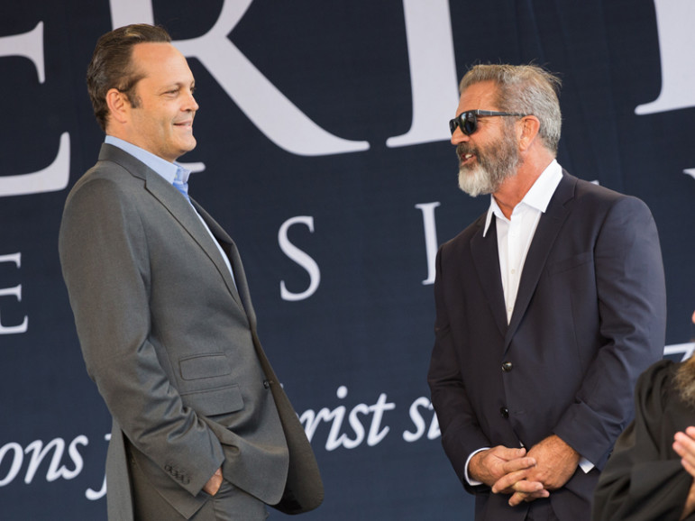 A-list actors Vince Vaughn and Mel Gibson converse behind TV star Willie Robertson at Liberty University's 2016 commencement. Photo by Mitchell Bryant, courtesy of Liberty University