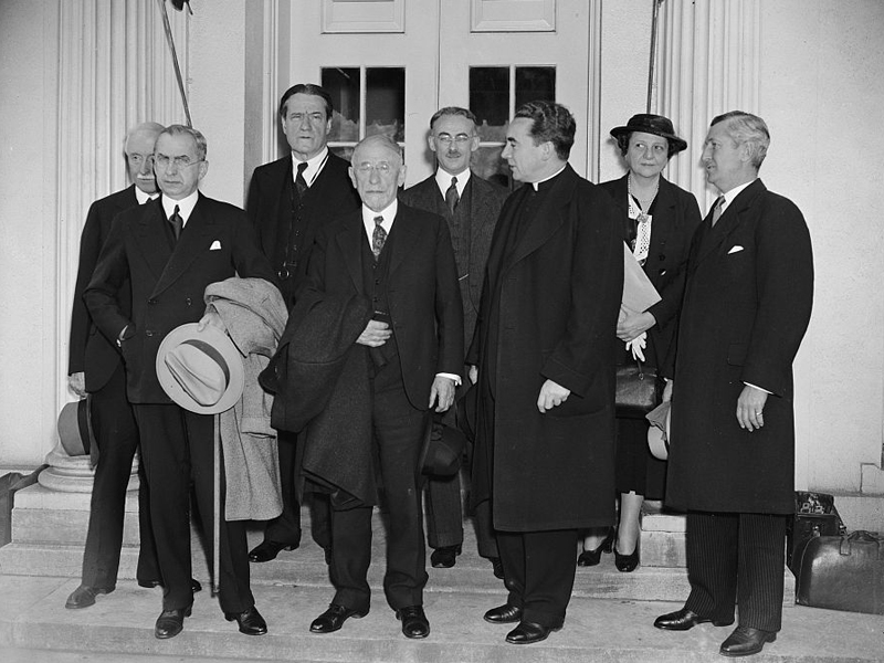 Experts on the refugee problem shown leaving the White House on April 13, 1938. After conferring with President Roosevelt, the group met with the President to go over preliminaries to an international conference to help political refugees from Germany and Austria. Left to right; Prof. Joseph P. Chamberlain, New York, Asst. Sec. of State Messersmith, Rabbi Stephen S. Wise, Henry Morgenthau, Rev. Samuel Cavert, New York, Rev. Michael J. Ready, Sec. of Labor Frances Perkins, and Lewis Kenedy, New York.
