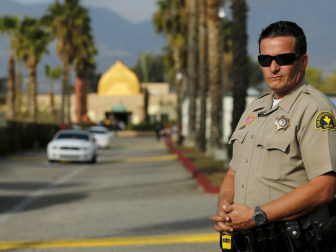 """A police officer stands watch as people leave Friday prayers at the Dar Al Uloom Al Islamiyah-Amer mosque where shooting suspect Syed Rizwan Farook was seen two to three times a week at lunch time, in San Bernardino, California on December 4, 2015. Authorities are investigating the San Bernardino, California, shooting as an """"act of terrorism"""", Federal Bureau of Investigation assistant director David Bowdich said at a news conference on Friday. Photo courtesy of REUTERS/Mike Blake"""