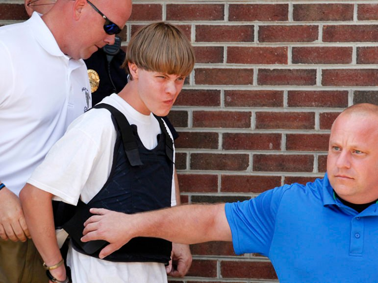 Police lead suspected shooter Dylann Roof, 21, into the courthouse in Shelby, North Carolina, on June 18, 2015. Roof, a 21-year-old with a criminal record, is accused of killing nine people at a Bible-study meeting in a historic African-American church in Charleston, South Carolina, in an attack U.S. officials are investigating as a hate crime. REUTERS/Jason Miczek