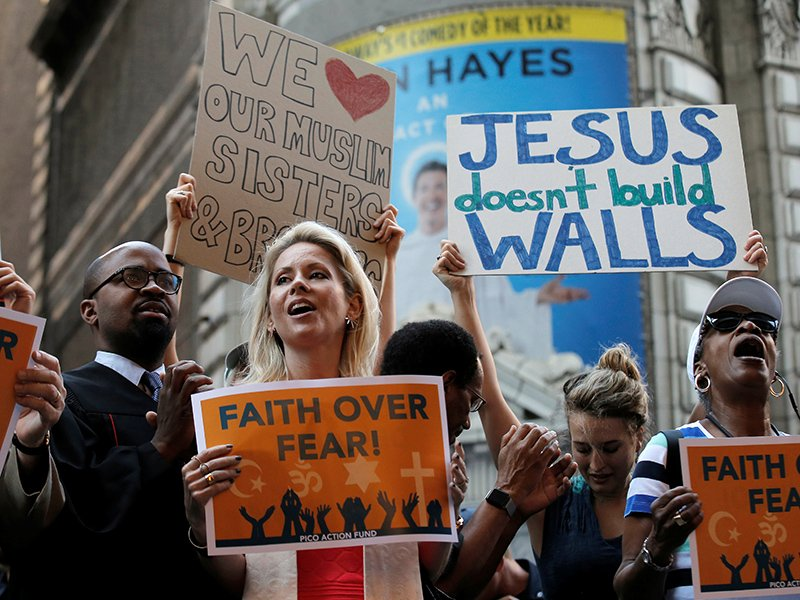 A group of interfaith religious leaders protest against Republican U.S. presidential candidate Donald Trump outside a hotel where he was to meet with evangelical leaders in New York