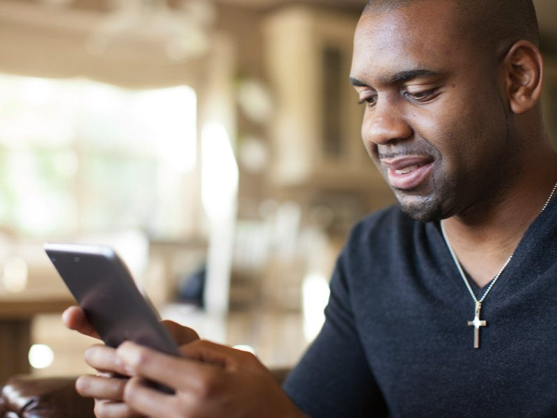 Man wearing cross looking at phone