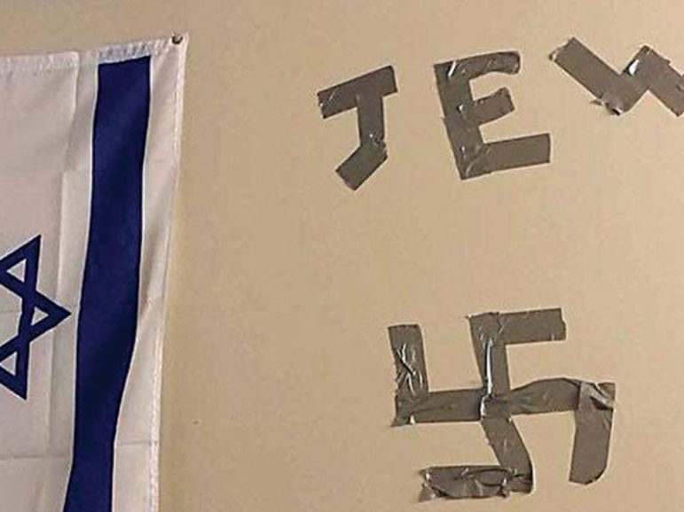 """At Drexel University in 2015, someone used tape to write """"Jew"""" and a swastika next to a student's Israeli flag. Photo courtesy of Anti-Defamation League"""