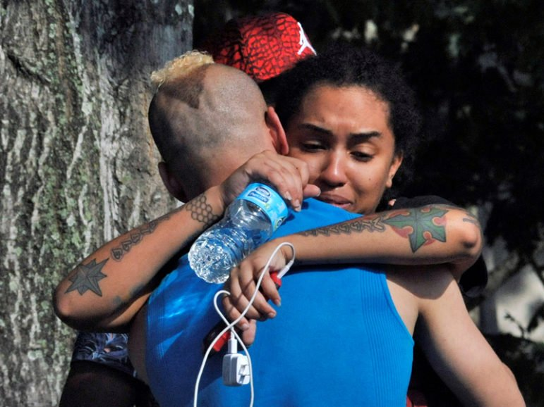 Friends and family members embrace outside the Orlando, Fla., police headquarters during the investigation of the deadly shooting at the Pulse nightclub, June 12, 2016.  Photo courtesy of REUTERS/Steve Nesius
