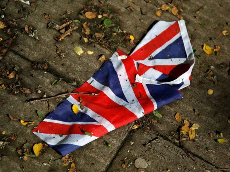A British flag which was washed away by heavy rains lies on the street in London June 24, 2016 after Britain voted to leave the European Union in the Brexit referendum. Photo courtesy of REUTERS/Reinhard Krause.