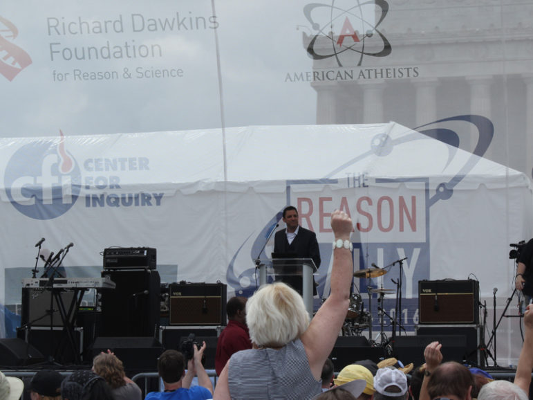 A woman raises her hand at Saturday's (June 4) Reason Rally in Washington, D.C. On the stage is American Atheist president David Silverman. RNS photo by Adelle M. Banks