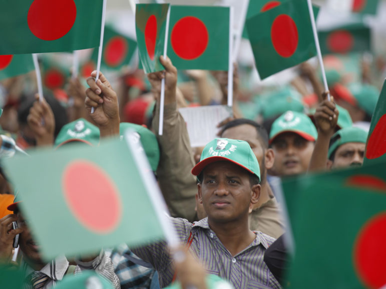 People wave the Bangladesh national flags as they prepare to rehearse singing the national anthem in an attempt to break a Guinness record at the national parade ground in Dhaka March 26, 2014. Photo courtesy REUTERS/Andrew Biraj
