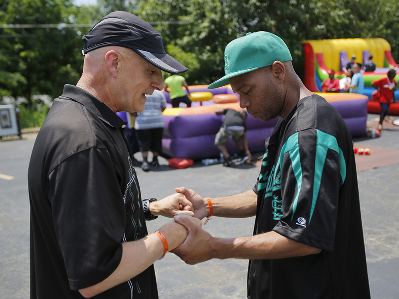 Rich Johnstone (left) prays with Ferguson, Mo., resident Jimmy at the Send Relief debut block party hosted by First Baptist Church of Ferguson. Johnstone serves as a North American Mission Board Send City Missionary for San Francisco and is a member of The Movement, a church plant in Oakland, Calif. Photo by John Swain, courtesy of Baptist Press