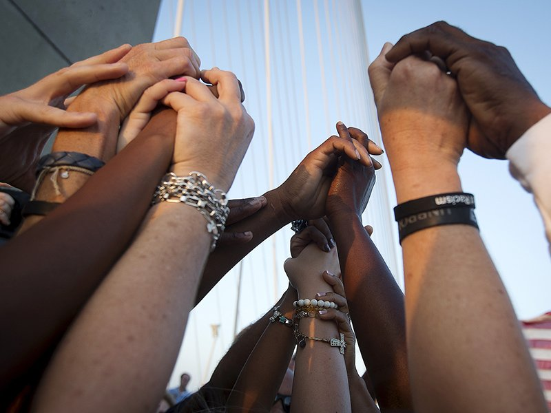 bd5443474 People of different races hold hands as they gather on the Arthur Ravenel  Jr. Bridge in Charleston