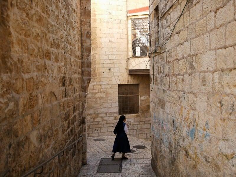 A nun walks in an alley