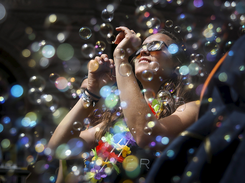 web a woman dances in a cloud of bubbles while marching in a gay pride parade - Gay Pride Christmas Decorations