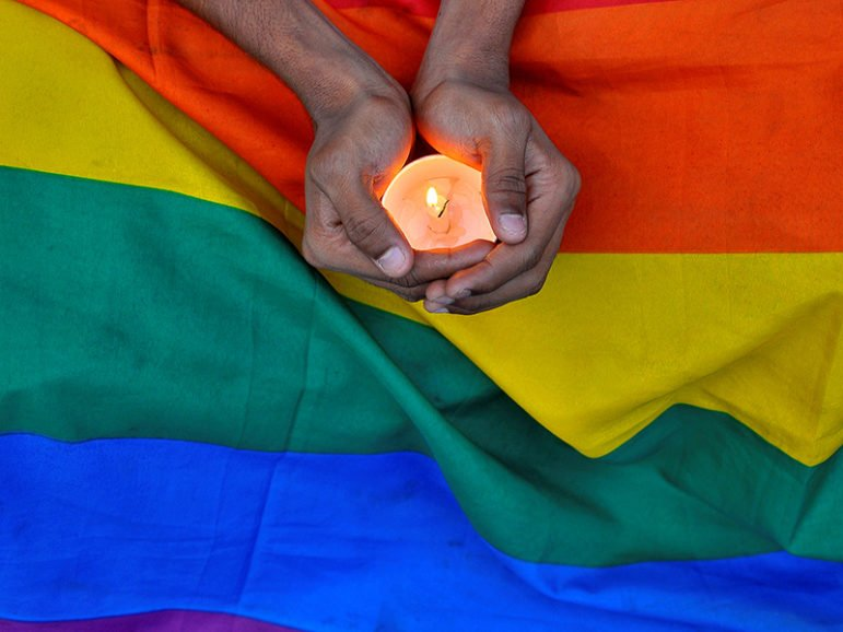 A member of the LGBT community holds a candle during a memorial service for victims of the mass shooting at the Pulse gay nightclub in Orlando, Fla. Photo courtesy of Rueters/Abhishek N.Cinnappa