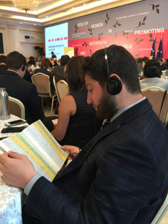 Eric Oppenheimer, one of ten young Jewish leaders from Tribe, listens to an English translator at Interfaith Kosovo. Religion News Service photo by Kimberly Winston