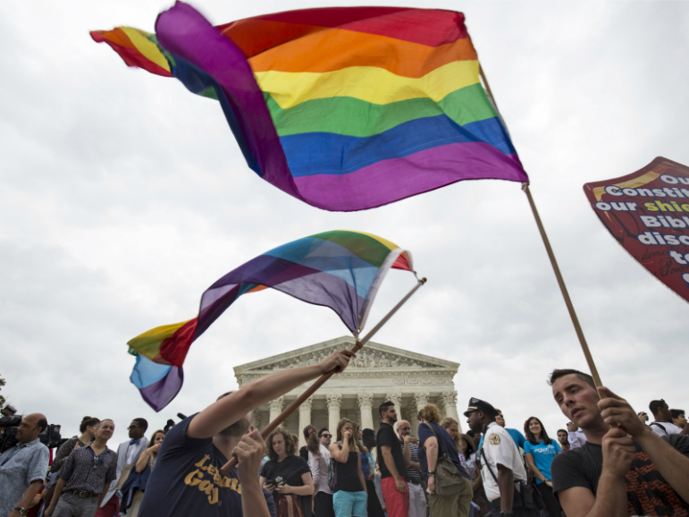 Supporters of gay marriage wave the rainbow flag after the U.S. Supreme Court ruled on June 26, 2015, that the U.S. Constitution provides same-sex couples the right to marry. The court ruled 5-4 that the Constitution's guarantees of due process and equal protection under the law mean that states cannot ban same-sex marriages. Photo courtesy of Reuters/Joshua Roberts