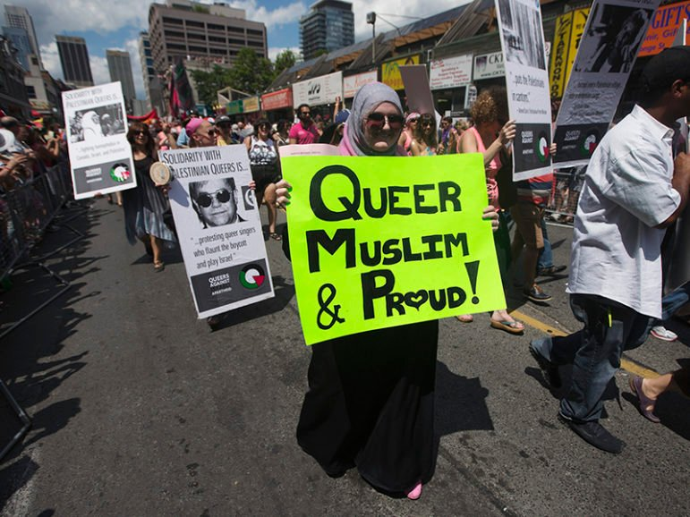 A woman carrying a sign that reads,