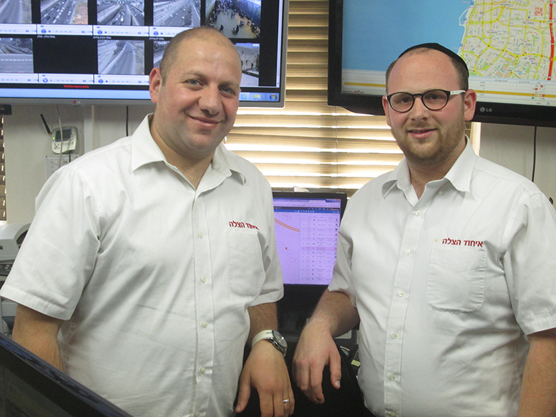 Ramzi Battash, left, a Muslim United Hatzalah dispatcher with Shlomo Mishkovsky, an ultra-Orthodox Jewish co-worker, in the crowded control room. RNS photo by Michele Chabin