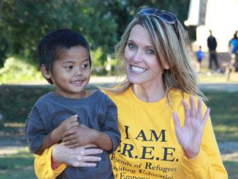 Kelli Czaykowsky waves while holding a refugee child on Oct 19, 2015. Photo courtesy of Allen Clark