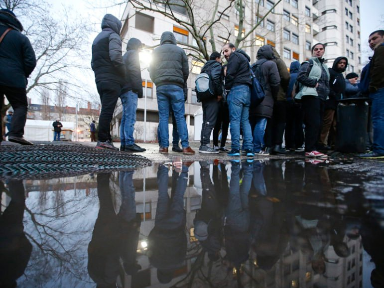 Migrants are reflected in a puddle as they queue in front of the Berlin Office of Health and Social Affairs for their registration process, early morning of Feb. 2, 2016.     REUTERS/Fabrizio Bensch - RTX2533D