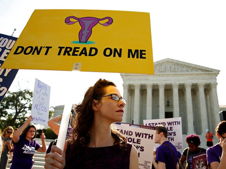 Demonstrators hold signs outside the U.S. Supreme Court as the court is due to issue its first major abortion ruling since 2007 on June 27, 2016. Photo by Kevin Lamarque/Reuters