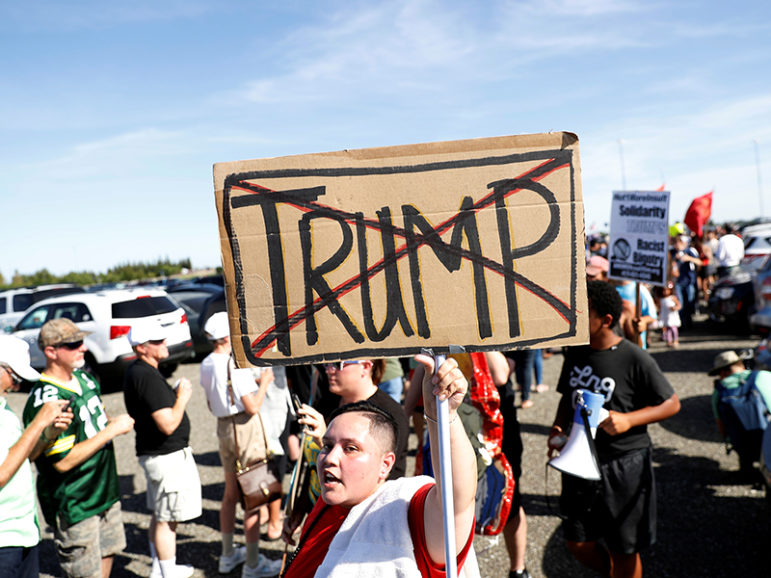 A demonstrator holds a sign against Republican presidential candidate Donald Trump outside his campaign rally in Sacramento, Calif., on June 1, 2016. Photo courtesy of REUTERS/Stephen Lam *Editors: This photo may only be republished with RNS-TRUMP-OPPONENTS, originally transmitted on June 21, 2016.