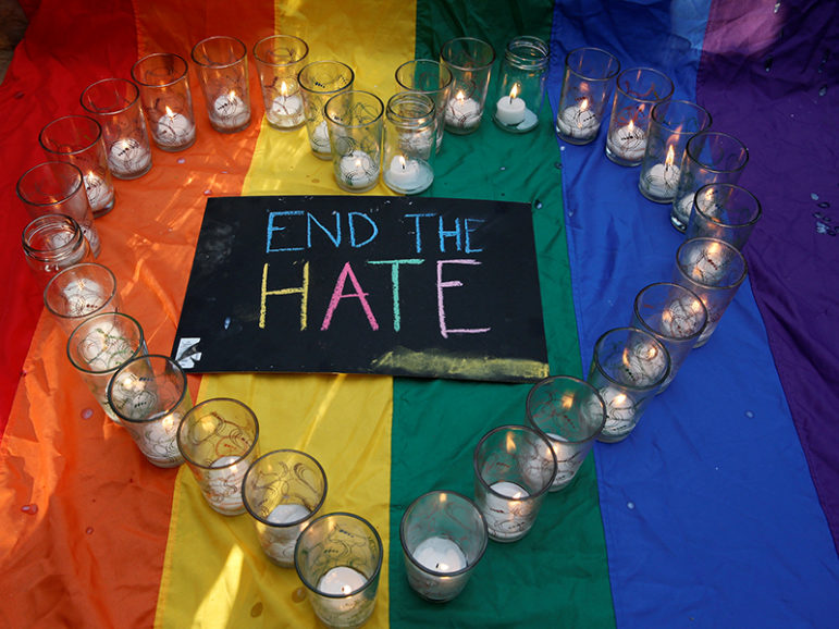 University of the Philippines students display glasses with lit candles and a placard as a tribute to those killed in the Pulse nightclub mass shooting in Orlando, Fla., during a protest at the school campus in Quezon city, Metro Manila, on June 14, 2016. Photo courtesy of REUTERS/Erik De Castro