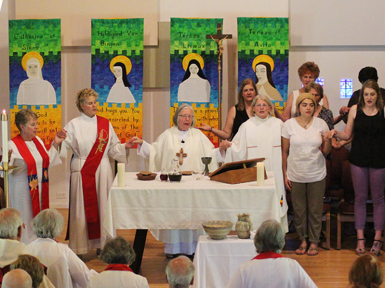Susan Vaickauski, center right, celebrates Communion alongside Presiding Bishop Joan Clark Houk, center left, of the Great Waters Region of Roman Catholic Womanpriests at her ordination to the priesthood on June 11, 2016, at the Northbrook United Methodist Church in Northbrook, Illinois. RNS photo by Emily McFarlan Miller