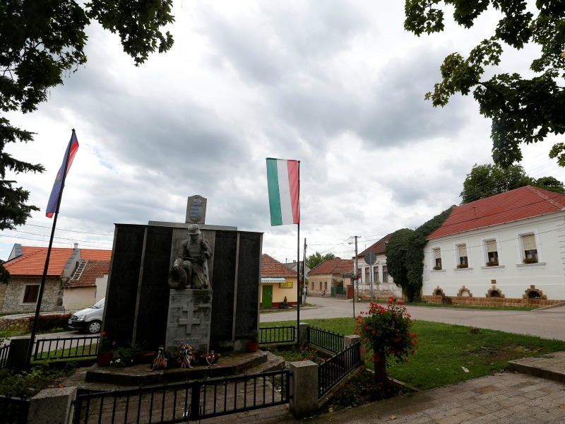 A view of the former home of the Zimmermann family in the village of Mad, Hungary, July 18, 2016, with a monument to the fallen heroes of the two World Wars in the foreground. Photo by Laszlo Balogh/REUTERS