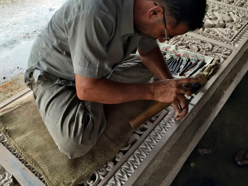 A worker engraves a stone