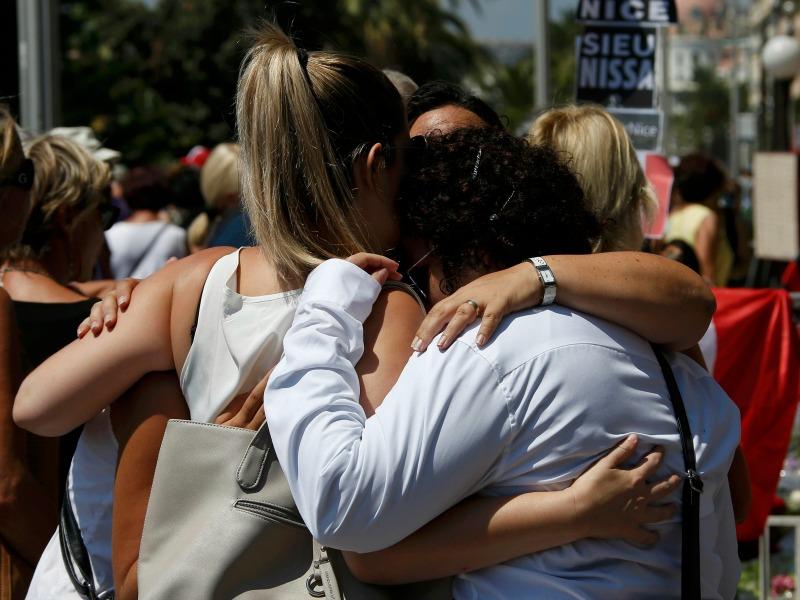 People hug on the Promenade des Anglais