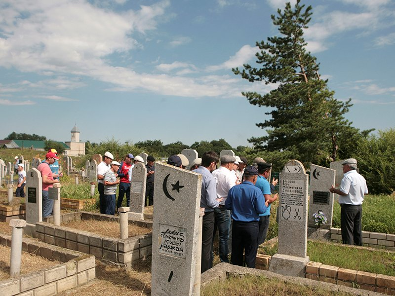 Local residents attend a prayer at the cemetery in the village of Ikon-Khalk