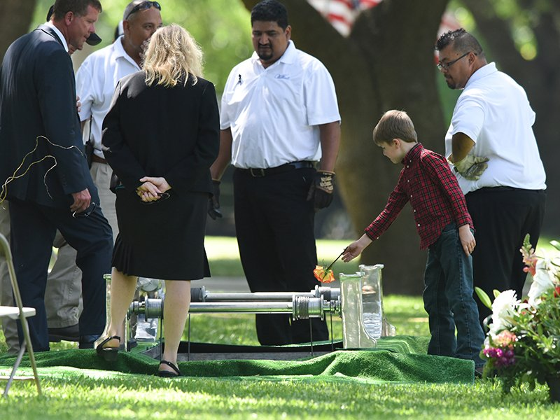 Magnus Ahrens drops a flower into the grave of his father, Dallas Police Department Senior Corporal Lorne B. Ahrens in Dallas