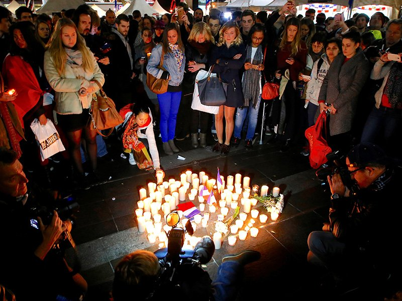 Members of the Australian French community stand around candles during a vigil in central Sydney