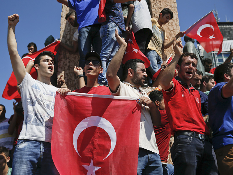 People wave Turkish flags as they stand around the Republic Monument in Taksim Square in Istanbul