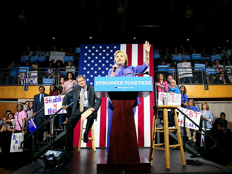 Presumptive Democratic presidential nominee Hillary Clinton speaks as U.S. Senator Sherrod Brown listens at the campus of the University of Cincinnati in Cincinnati