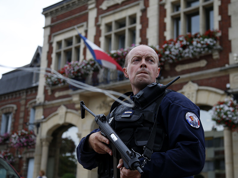 A policeman secures the position in front of the city hall after two assailants had taken five people hostage in the church at Saint-Etienne-du -Rouvray near Rouen in Normandy