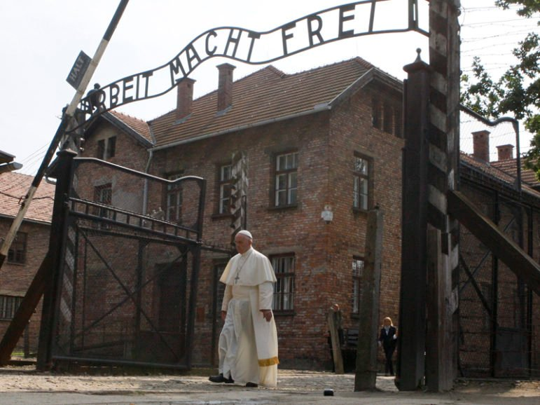 """Pope Francis walks through a gate with the words """"Arbeit macht frei"""" (Work sets you free) at the former Nazi German concentration and extermination camp Auschwitz-Birkenau in Oswiecim, Poland, July 29, 2016. Photo courtesy REUTERS/Kacper Pempel. Editors: This photo may only be used with RNS-POPE-AUSCHWITZ, published July 29, 2016."""