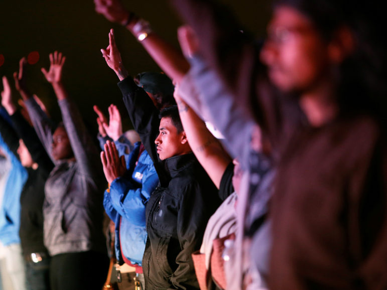 Demonstrators raise their hands toward a line of police officers on Highway 880 in Oakland, Calif., during a protest on July 7, 2016 against the police shootings that led to two deaths in Louisiana and Minnesota. Photo courtesy Reuters/Stephen Lam