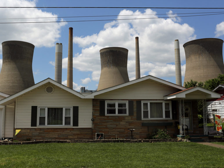 The John Amos coal-fired power plant is seen behind a home in Poca, W.Va., on May 18, 2014. Photo courtesy of REUTERS/Robert Galbraith