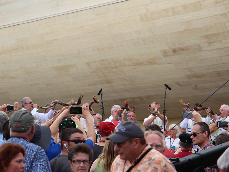 Supporters watch on the big screen as several men blow shofars at the foot of the full-scale replica of Noah's Ark during a ribbon cutting event at the Ark Encounter on July 5, 2016, in Williamstown, Ky. RNS photo by Emily McFarlan Miller