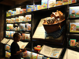 "A young visitor observes an exhibit titled ""Fairy Tale Ark"" aboard the full-scale Noah's Ark replica at the Ark Encounter during a preview of the park on July 5, 2016, in Williamstown, Ky. The exhibit displays toys and books recounting the biblical flood account as a children's story alongside the words, circled by a snake representing Satan, ""If I can convince you that the flood was not real, then I can convince you that heaven and hell are not real."" RNS photo by Emily McFarlan Miller"