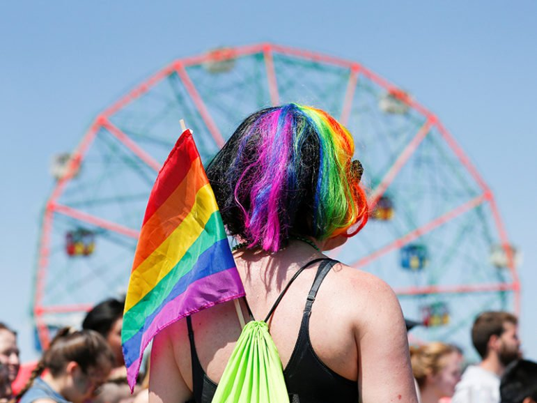 A participant wears an LGBT flag as people take part in the annual Mermaid Parade in Brooklyn, N.Y., on June 18, 2016. REUTERS/Eduardo Munoz - RTX2GYSR