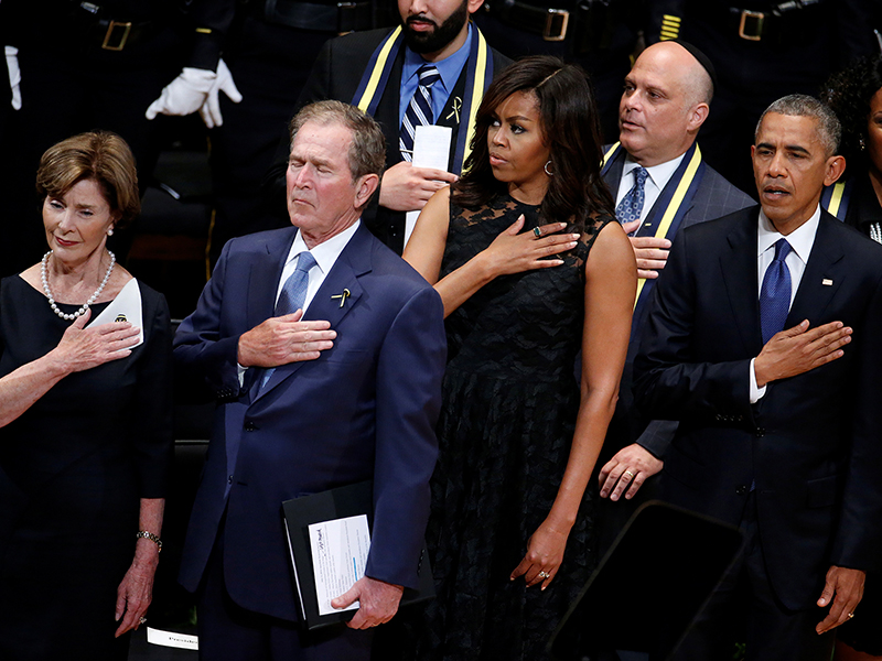Former First Lady Laura Bush (L), former President George Bush (2nd L), First Lady Michelle Obama (3rd L) and U.S. President Barack Obama (R) hold their hands on their hearts as they sing the national anthem at a memorial service following the multiple police shootings in Dallas, on July 12, 2016. Photo courtesy of REUTERS/Carlo Allegri